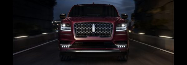 A 2019 Lincoln Navigator driving down a highway at night